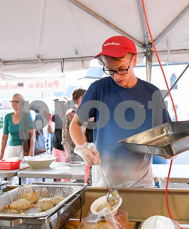 062317 Wesley Bunnell | Staff A volunteer pieces together the most popular dish the food tent named the polish platter on Friday evening June 23 at the Sacred Heart Festival.