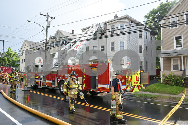 062717 Wesley Bunnell | Staff A fire broke out Tuesday afternoon at 404 East St in New Britain on the top floor. Firefighters descended from the building and prepare to put their gear away.