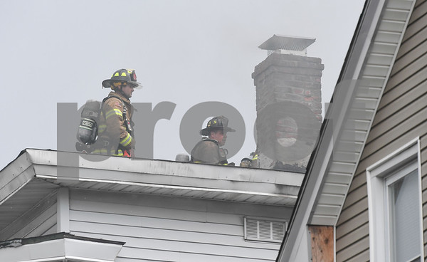 062717 Wesley Bunnell | Staff A fire broke out Tuesday afternoon at 404 East St in New Britain on the top floor. Firefighters walk from the ladder truck to the back of the home.