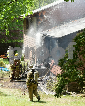 060217 Wesley Bunnell | Staff Fire destroyed a raised ranch home at 186 Ellsworth Blvd around noon time on Friday in the Kensington section of Berlin. Multiple fire departments responded including Berlin, Newington, Meriden, Cromwell, Rocky Hill & Wethersfield. Firefighters spray water onto the back of the home.