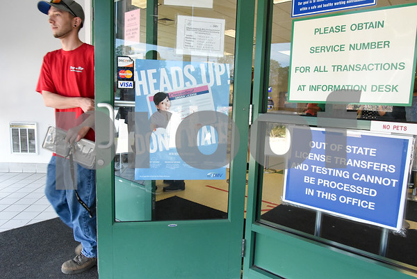 061317 Wesley Bunnell | Staff Daniel Duksa of New Britain leaves the DMV office on Mountain Rd on Tuesday afternoon. Visible on the door is information regarding the new license renewal program.