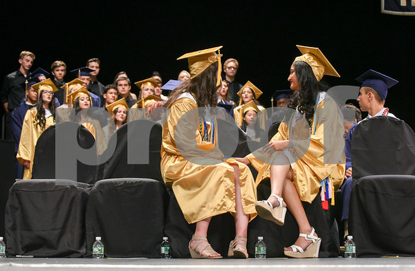 062017 Wesley Bunnell | Staff Newington High School held their 2017 commencement at the Oakdale Theatre on Tuesday evening. Class Valedictorian Teodora Markova, L, sits with Salutatorian Ariya Jacob as they listen to the school chorus.
