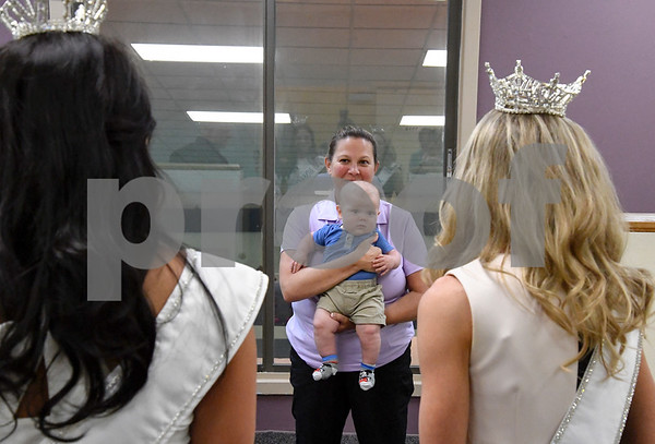 062617 Wesley Bunnell | Staff Healthtrax membership advisor Nicole Elliot holds her son Ryan, age 4 months, as newly crowned Miss CT Teen Brooke Eve Cyr, L, and Miss CT Eliza Lynne Kanner, stop to talk during a tour of Healthtrax in Bristol on Monday afternoon.