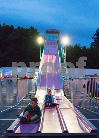 061517 Wesley Bunnell | Staff The first day of the Holy Cross Bazaar took place Thursday evening in the parking lot of the St. Pope John Paul II School. Five year old Abby Weatherbee, middle, nears the end of the slide.