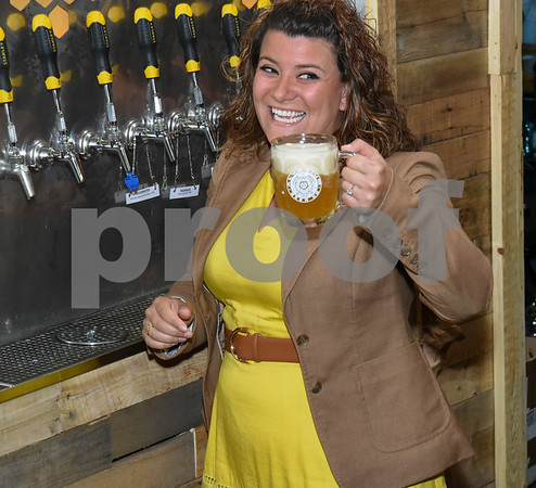 062317 Wesley Bunnell | Staff Alvarium Beer Company held a ribbon cutting on Friday and became the first brewery open in New Britain since the mid 1950's. Mayor Erin Stewart laughs as she finishes pouring a beer from of the taps lining the wall.