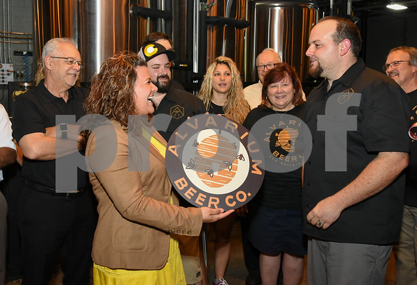 062317 Wesley Bunnell | Staff Alvarium Beer Company held a ribbon cutting on Friday and became the first brewery open in New Britain since the mid 1950's. Mayor Erin Stewart is presented with her own Alvarium Beer sign from Alvarium co-founder Mike Larson, R.
