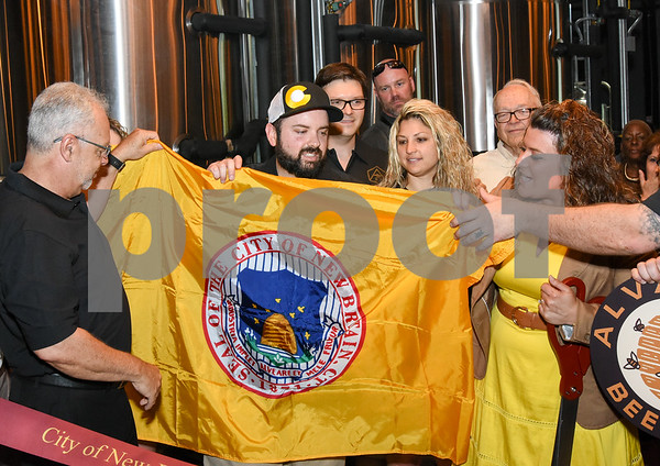 062317 Wesley Bunnell | Staff Alvarium Beer Company held a ribbon cutting on Friday and became the first brewery open in New Britain since the mid 1950's. Economic Development Director Bill Carrol, L, helps hold a City of New Britain flag along with Alvarium Beer co-founder Chris DeGasero, co-founder Brian Bugnacki, and Mayor Erin Stewart , right.