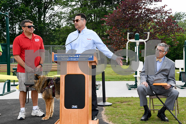 062917 Wesley Bunnell | Staff Newington Parks and Recreation Superintendent Bill DeMaio , L, stands next to Saputo plant manager Roque Lopez as he gives his remarks prior to the ribbon cutting for the Saputo Fitness Center located near the town pool in Mill Pond Park. Mayor Roy Zartarian sits to the right.