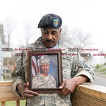 032316   Wesley Bunnell | Staff  Wearing his son Julian's Army jacket and beret Selwyn Cartie stands on his front porch holding Julian's photo & discussing the circumstances of his death.
