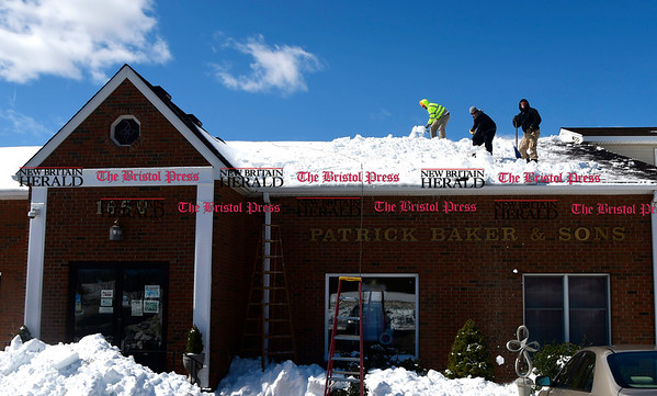 3/16/2017 Mike Orazzi | Staff Pat Kelly, Nathan Savage and Richard Nadeau while clearing snow from the roof of Patrick Baker & Sons on West Street in Southington Thursday afternoon.