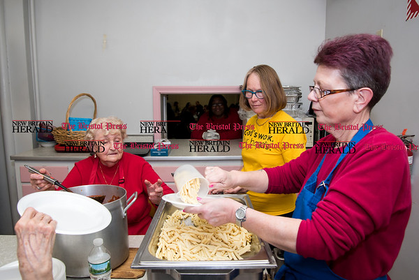030817 Wesley Bunnell | Staff First Lutheran Church in New Britain is running short of the money needed to hold their pasta supper as they have every Wednesday night to feed the homeless. From the left Shirley Hiser waits to ladle her home made sauce as Nancy Peterson, right, prepares to hand off a plate.