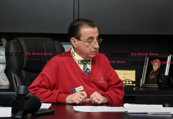 030717 Wesley Bunnell | Staff Salesman Gerald Campana of Acura of Berlin in his office on March 7 as he helps a couple prepare their financial paperwork.