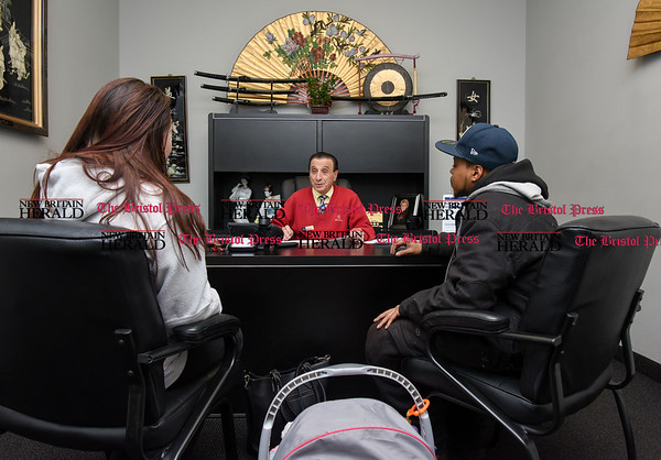 030717 Wesley Bunnell | Staff Kyron Halley, left, sits with Brianna Valeriano and their 6 month old daughter Avery as they discuss their car purchase with salesman Gerald Campana at Acura of Berlin on March 7.