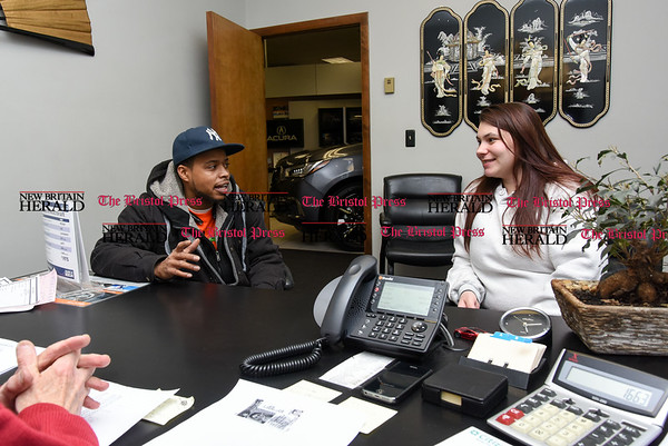 030717 Wesley Bunnell | Staff Kyron Halley, left, sits with Brianna Valeriano as they discuss their car purchase with salesman Gerald Campana at Acura of Berlin on March 7.