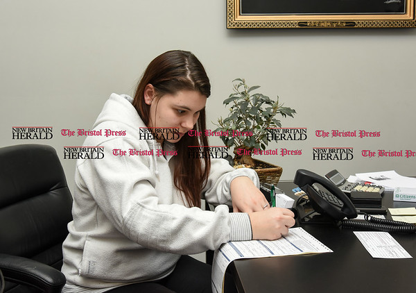 030717 Wesley Bunnell | Staff Brianna Valeriano fills out paperwork inside of Acura of Berlin on March 7.