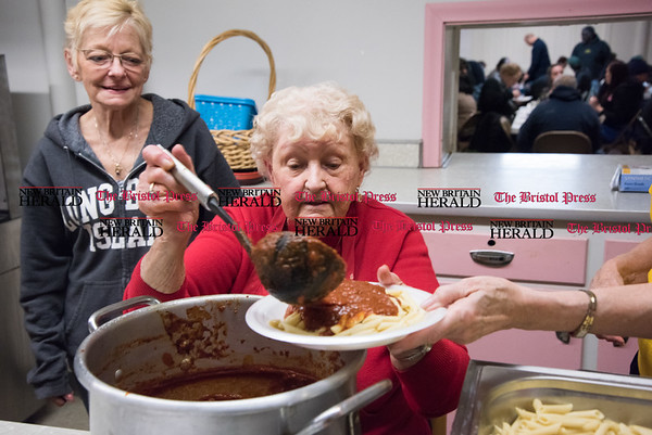 030817 Wesley Bunnell | Staff First Lutheran Church in New Britain is running short of the money needed to hold their pasta supper as they have every Wednesday night to feed the homeless. Shirley Hiser ladles her home made sauce over a plate of pasts to be served as Gail Spada looks on.
