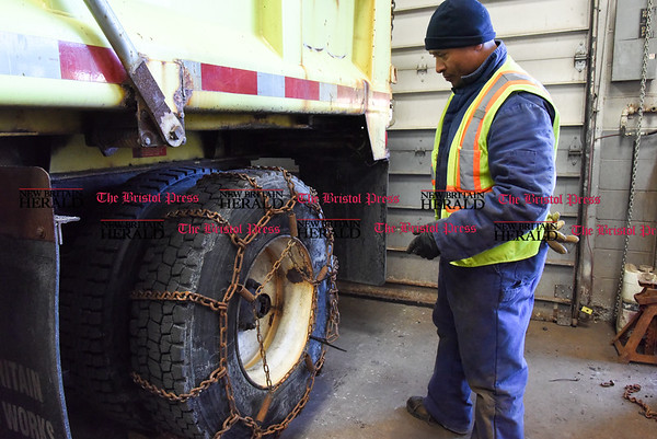 031317 Wesley Bunnell | Staff New Britain's Public Works Department was busy Monday March 13 preparing vehicles for the upcoming storm. Tim McCrorey puts the finishing touches on attaching chains to a truck tire.