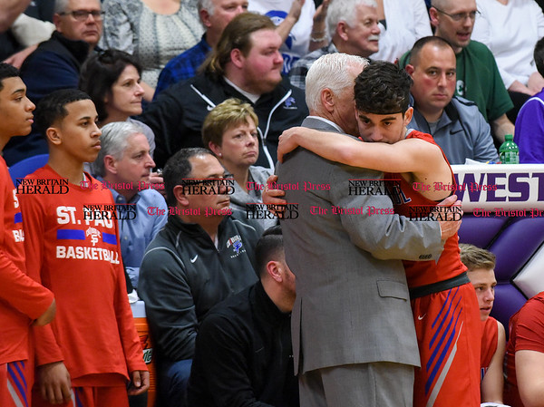 031317 Wesley Bunnell | Staff St. Paul boys basketball was defeated in a Class S CIAC playoff game against Westbrook on Monday March 13. Elijah Kennedy (4) receives a hug and words from Head Coach Steve Phelps as he exits the game.