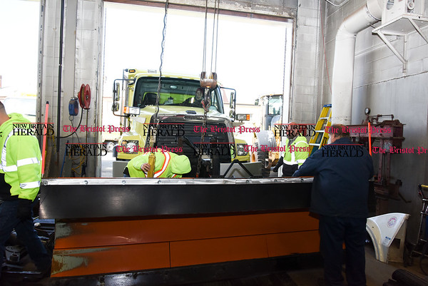 031317 Wesley Bunnell | Staff New Britain's Public Works Department was busy Monday March 13 preparing vehicles for the upcoming storm. A plow is ready to be attached to a city truck. Starting third from the left are Domenic Mutone and Bill LaForest.