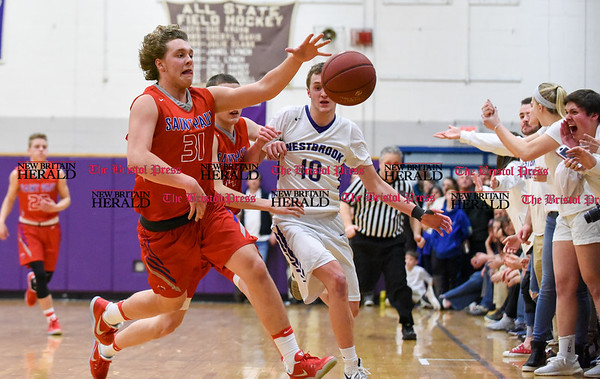 031317 Wesley Bunnell | Staff St. Paul boys basketball was defeated in a Class S CIAC playoff game against Westbrook on Monday March 13. Darek Wiecki (31) and Tyler Arbuckle (14) track down a loose ball in a tightly packed gym lined with fans close to the court.