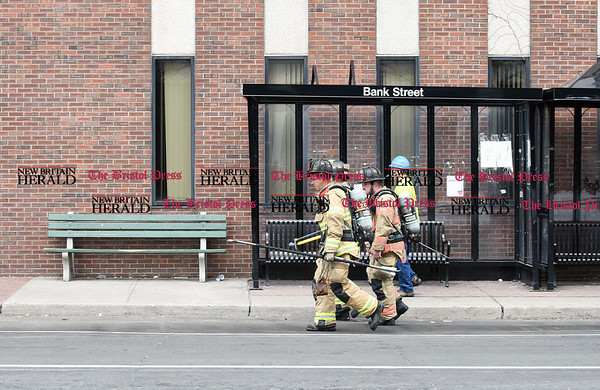 032117 Wesley Bunnell   Staff The New Britain Fire Department investigated a possible gas leak at 267 Main St on March 21, 2017. Fire and gas workers walk down Bank St towards the front of the building.