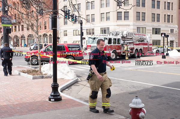 032117 Wesley Bunnell | Staff The New Britain Fire Department investigated a possible gas leak at 267 Main St on March 21, 2017. A firefighter puts up yellow caution tape down a portion of Bank St on the side of the building.