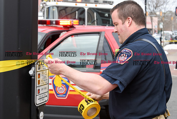 032117 Wesley Bunnell | Staff The New Britain Fire Department investigated a possible gas leak at 267 Main St on March 21, 2017. A fire official puts up barrier tape on Bank St across from the building.