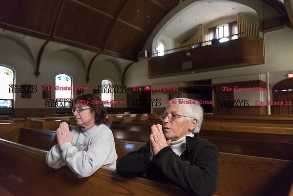 032417 Wesley Bunnell | Staff Mary Scalise , left, prays with Teresa Pistritto at St. Paul's Church in Kensington on March 24, 2017. St. Paul's and Sacred Heart in East Berlin have merged leading to the eventual closing of Sacred Heart.