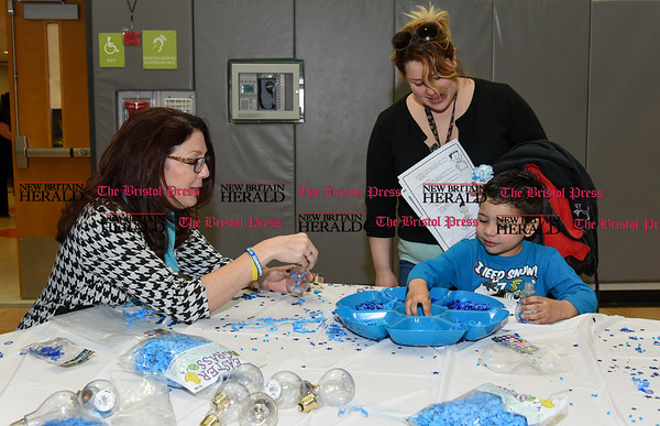 033017 Wesley Bunnell | Staff Gaffney Elementary School held their 7th annual Family Autism Dinner on Wednesday evening. The dinner brings together families, teachers, staff members and volunteers together to socialize with loved ones with autism. Board of Education member Sharon Beloin-Saavedra makes toy lightbulbs with 4 year old Bronson Baez while Bronson's mother Yva Carrion watches.