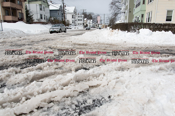031517 Wesley Bunnell | Staff Many of the roads including the intersection of Day and East St in New Britain were covered in slushy snow making driving difficult the day after heavy snow on Wednesday March 15.