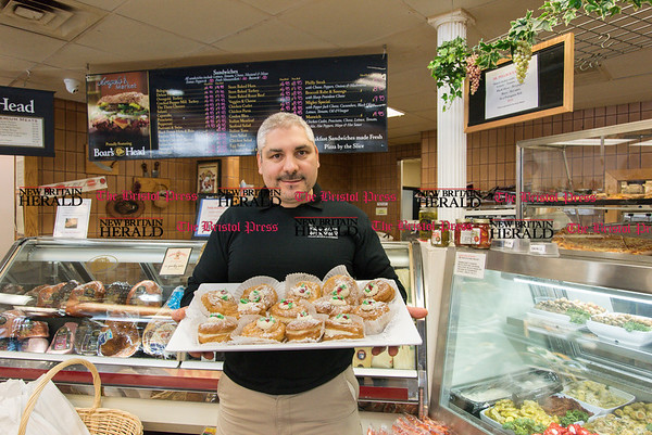 031717 Wesley Bunnell | Staff Owner Joe Tropea of Angelo's Market with a tray of zeppole which are traditionally made in celebration of St. Joseph's Day
