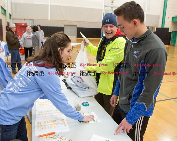 Meg Fanion, left, checks in Randy Willis, center, of Southington, and Adrian Gasior, right, of Bristol, before the 15th Annual Shamrock Run in Bristol, Mar. 18, 2017. (Photo by Christopher Zajac)