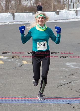 Mary-Lynn Currier, of Burlington, crosses the finish line to clinch overall female first place finisher of the five mile course of the Shamrock Run in Bristol on March 18 , 2017. (Photo by Christopher Zajac)