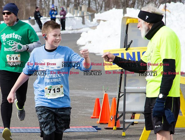 Ryan Biggs, left, of Harwington, gets a fist bump as he crosses the finish line from Bob Ward, right, of Vernon, at the end of the five mile course of the Shamrock Run on March 18, 2017. Biggs finished first in his 11-13 years boys age group. (Photo by Christopher Zajac)