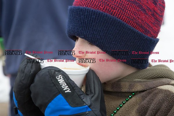 Lincoln Archibald, of Bristol, sips some hot soup after completing the two mile course at the Shamrock Run in Bristol on March 18, 2017. The hot soup was a welcome treat in the below freezing temperatures. (Photo by Christopher Zajac)