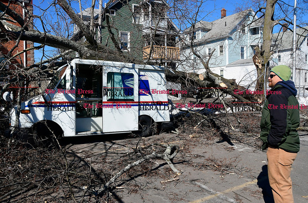 3/22/2017 Mike Orazzi | Staff Nicholas Roy surveys the damage after a Norway Maple tree fell on a US Postal service truck in Bristol Wednesday morning.