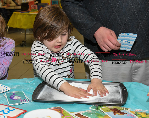 033017 Wesley Bunnell | Staff Parent Learning Night or Curriculum Night was held at Roosevelt Early Learning Center on Thursday night. Teachers set up tables for parents to visit with their children in various subjects to better help parents understand their child's needs at home. Audrey Quinn, age 4, makes handprints in salt at the tactile table.