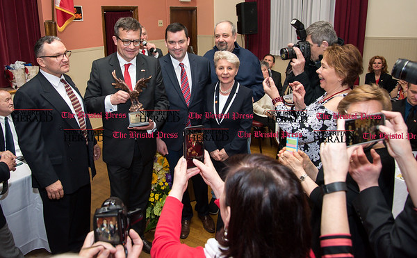 033117 Wesley Bunnell | Staff Polish Ambassador Piotr Wilczek visited New Britain's Little Poland section on Friday March 31, 2017 to celebrate the opening of an honorary Polish Consul in the city. Ambassador Piotr Wilczek, second from left, is crowed by guests eager to grab a photograph after being presented with an eagle award from Polonia Business Association which was presented by Attorney Adrian Baron, third from the left.
