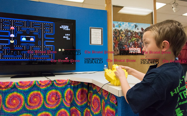 033117 Wesley Bunnell | Staff Celebrating its 60th anniversary the New Britain Youth Museum is holding a new exhibit titled A Blast From the Past 60 Years. The exhibit has exhibits broken up by the decade featuring popular culture. 7 year old James Arni Jr. plays pacman at the 80's exhibit.