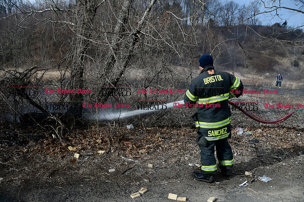 3/3/2017 Mike Orazzi   Staff Bristol firefighters extinguish a brush fire along Farrell Avenue in Bristol Friday afternoon.
