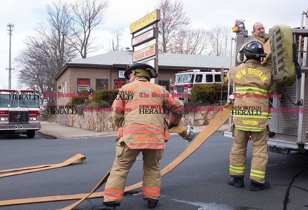 030317 Wesley Bunnell   Staff New Britain Firefighters pack up equipment after putting out a fire at the Big Daddy 2 Laundromat at 145 Stanley St on Friday March 3.