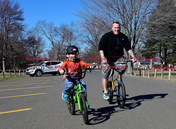 3/8/207 Mike Orazzi | Staff Chris Dayton and his son Ben,7, ride their bikes in Plainville's Norton Park while enjoying Wednesday's warm temperatures.