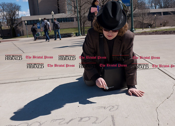 030817 Wesley Bunnell | Staff A rally was held on CCSU's campus in solidarity with the International Women's Strike at noon on Wed March 8. Sophomore English major Mason Quinn writes a show of support in chalk among with several other rally participants.