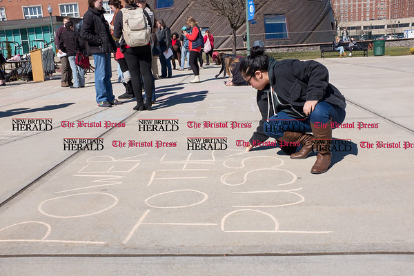 030817 Wesley Bunnell | Staff A rally was held on CCSU's campus in solidarity with the International Women's Strike at noon on Wed March 8. Senior Katherine Cotuc writes a message of support with for rally organizers on the sidewalk near the student center at the conclusion of the event.
