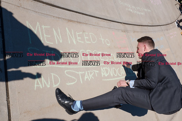 030817 Wesley Bunnell | Staff A rally was held on CCSU's campus in solidarity with the International Women's Strike at noon on Wed March 8. Junior Brendan Kruh writes a message of support among many others on the sidewalk near the student union.