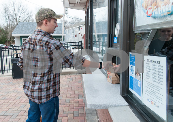 03/01/18 Wesley Bunnell | Staff Berlin High School student Richard Scalora is handed his order at Dairy Queen in Kensington on its first day of business for 2018 on Thursday.