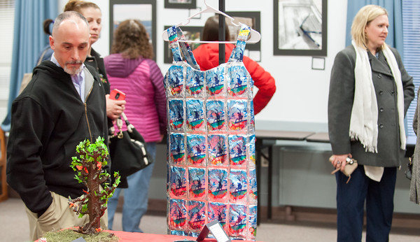 03/27/18 Wesley Bunnell | Staff In honor of March being Youth Art Month, Berlin High School AP Studio Art is holding a showing of student work beginning on Monday, March 26th running through Friday, March 30th at the Berlin Peck Library. Visitors walk past a dress made from Capri Sun pouches by Senior Madison Marolda.