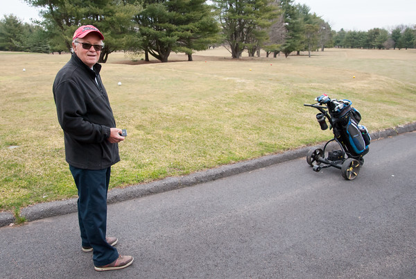 03/29/18 Wesley Bunnell | Staff Ed Rosario uses a remote control to control his battery powered electric golf cart at Stanley Golf Course on opening day Thursday morning.
