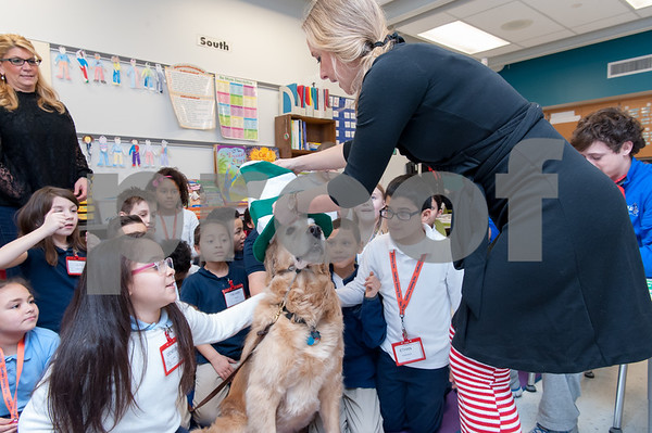 03/02/18 Wesley Bunnell | Staff Reading teacher Dorothy Dziedzic places a hat on therapy dog Cooper with the help of Genesis Lopez, L, and Ethan Rodriguez, R, on Friday during Dr. Seuss Day aka Read Across America Day. The students are part of Ms. Libby's third grade class while Cooper is also the personal dog of Principal Anita Fazio, far L.