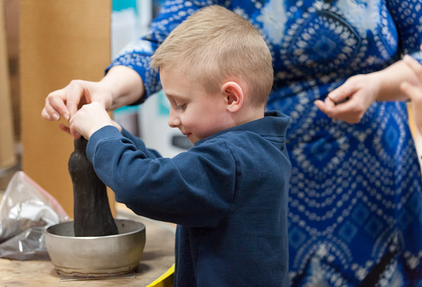 03/27/18 Wesley Bunnell | Staff First grade teacher Mrs. Poff helps student Austin Greener with the magnetic slime exhibit during the Smalley Academy 2nd Annual Smalley Science Fair on Tuesday morning featuring science exhibits by all grades.